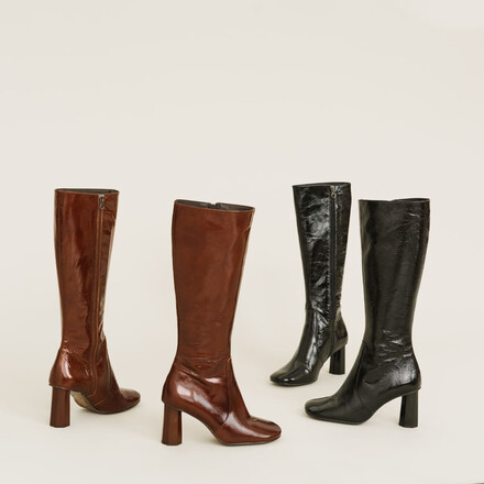 Heeled high boots in black old looking leather